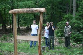 Menschen stehen vor einem Holzrahmen im Wald